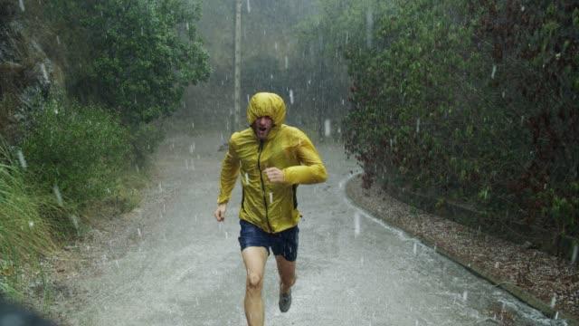 vídeos de stock e filmes b-roll de athletic man jogging in extreme weather condition. hail and rain - dedicação