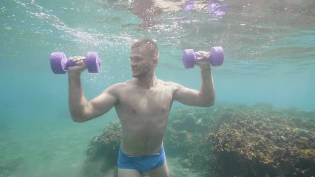 Athletic man makes sport exercise with dumbbells underwater stands on ocean floor.