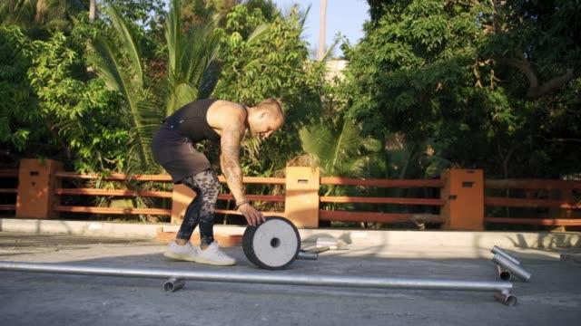 vídeos de stock, filmes e b-roll de homem atlético malhando em uma academia ao ar livre. força e motivação - comodidades para lazer