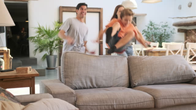 Atletische moeder en jonge kinderen die over Rug van Bank springen video