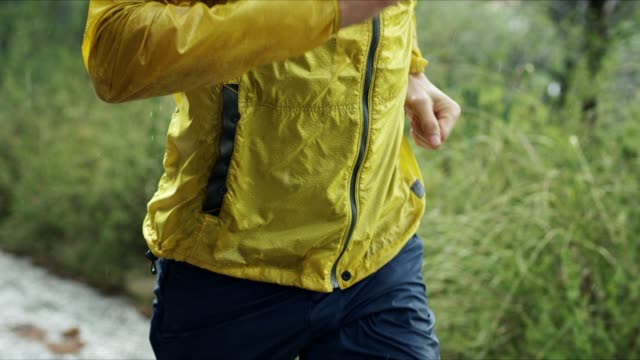 athletic muscular young man in sports outfit is jogging in the street on a rain - dedizione video stock e b–roll