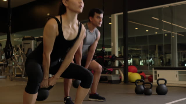 athletic people playing dumbbell exercise for arm endurance training exercise to strengthen and tone the shoulder muscles. 4k resolution. - giria filmów i materiałów b-roll