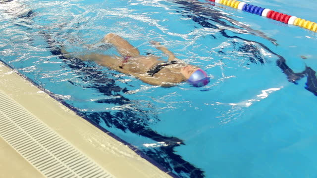 Athletic pregnant woman floating on back in pool. video