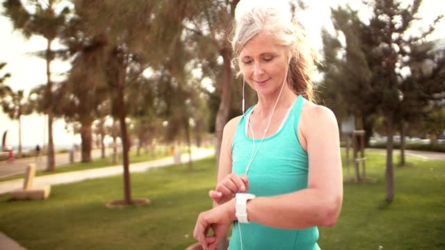 Athletic senior woman monitoring her running performance on smartwatch video