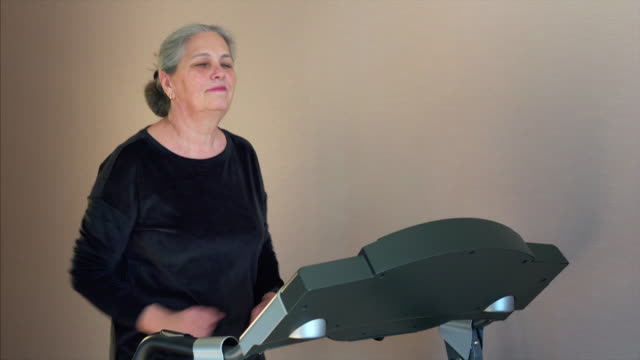 athletic senior woman running on treadmill. training her endurance, cardio - runner rehab gym video stock e b–roll