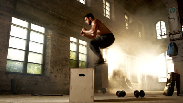 athletic shirtless fit man energetically box jumps in hardcore gym doing part of cross fitness training program. man is sweaty from intense workout/ exercise, gym is in industrial factory location. - irriducibilità video stock e b–roll