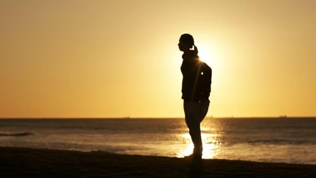 vidéos et rushes de cintrée athlétique jeune femme faisant de l'exercice et d'étirement dans le parc en plein air - joggeuse