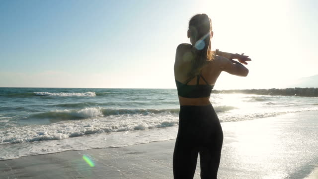 Video Athletic woman at the beach stretching and relaxing after her workout