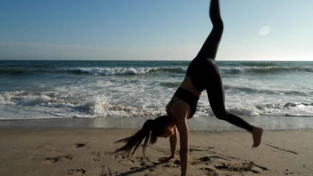 Athletic woman does a handstand on the beach