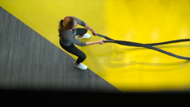 Athletic woman doing battle ropes exercise in a health club Exercise,Gym,Japan, UK, USA, 4K Resolution, Adult cross training stock videos & royalty-free footage