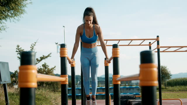 SLO MO Athletic woman doing exercises on the parallel bars
