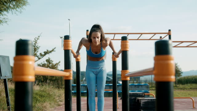SLO MO Athletic woman doing push ups on the parallel bars
