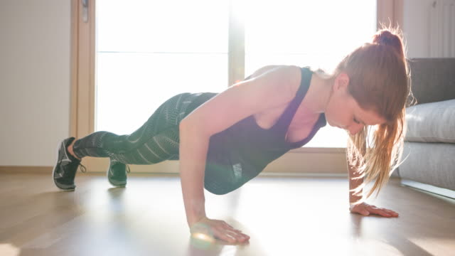 Athletic woman doing push-ups at home Young muscular fitness woman doing calisthenic exercises, push-ups, at home on living room floor push ups stock videos & royalty-free footage
