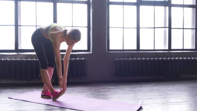 vídeos de stock, filmes e b-roll de mulher atlética fazendo exercícios de alongamento. mulher em forma fazendo seu alongamento de yoga pré-treino - comodidades para lazer