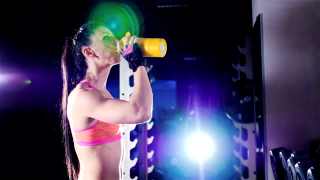 Athletic woman drinking a protein shake in a shaker in the gym. In the rays of spotlights. Sports nutrition video