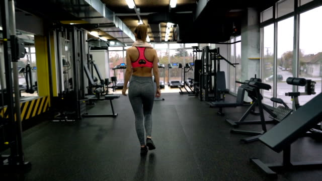 Athletic woman entering a gym and exercising on lateral pull-down weights exercise machine. video