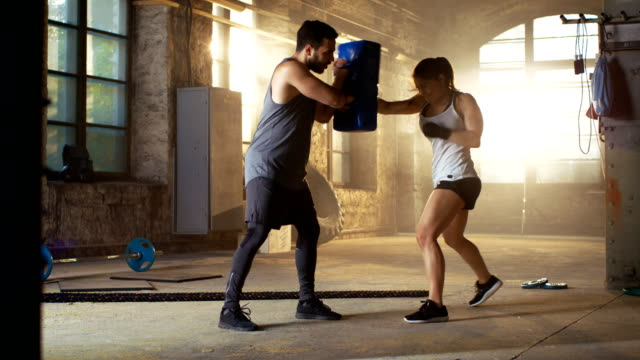 sportliche frau hits boxsack, ihrem lebensgefährten / trainer hält. sie ist professionelle kämpfer und training in einem fitnessstudio. - boxen sport stock-videos und b-roll-filmmaterial