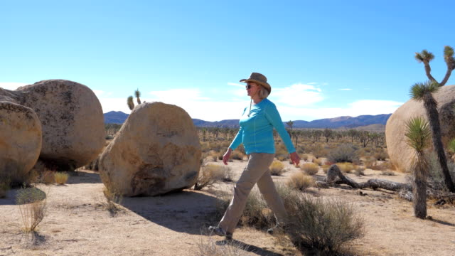 Athletic Woman In A Cowboy Hat Goes On A Mojave Desert, Jumps Through The Bushes video