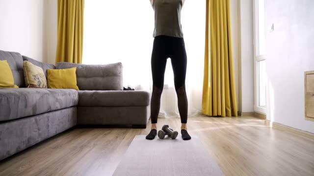 atletisk kvinna i sportkläder uppvärmning, stretching gör fitness hemma - working from home bildbanksvideor och videomaterial från bakom kulisserna