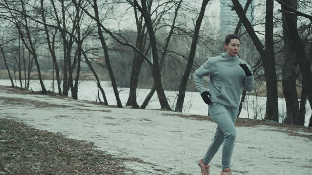 Athletic woman jogging in city park in winter video