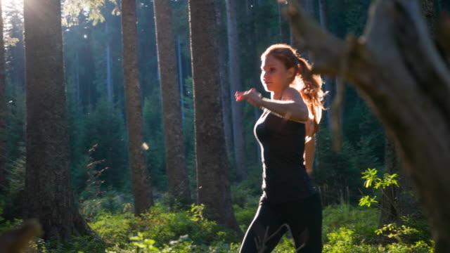 athletic woman jogging in forest - posizione corretta video stock e b–roll
