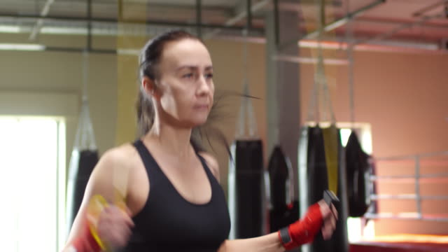 Athletic Woman Jumping Rope in Boxing Gym