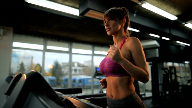 athletic woman running on treadmill in a gym. - reggiseno sportivo video stock e b–roll