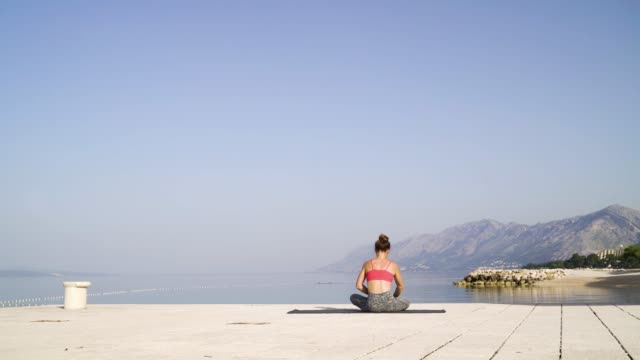 Athletic woman sitting in lotus pose on sea pier