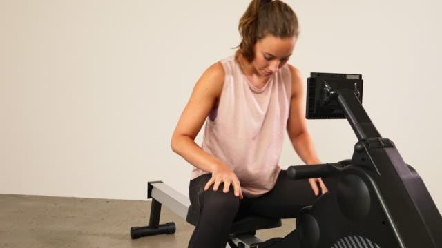 トレーニングのためのローイングマシン上のアスレチック女性ストラップフィート - 機械類点の映像素材/bロール