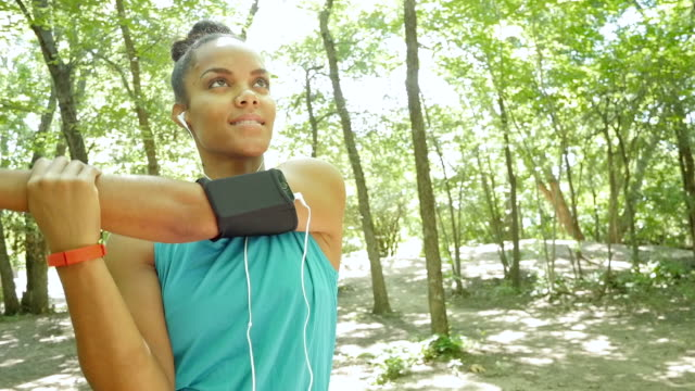 Athletic woman stretching before off road running in park Young adult African American runner is stretching and warming up her muscles before running off road in wooded park. She is on a dirt path surrounded by green trees. Woman is wearing a blue athletic tank and an mp3 player in an armband. She is also wearing a fitbit. tank top stock videos & royalty-free footage