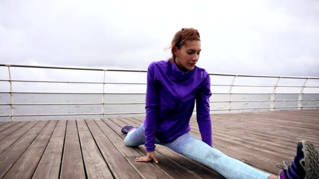 Athletic woman stretching her legs before a jog on the beach by the sea early in the morning. Young girl doing splits. Training by the beach in summer video