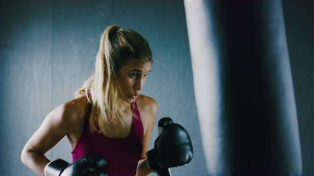 athletic woman training kickboxing in the gym - kick boxing video stock e b–roll