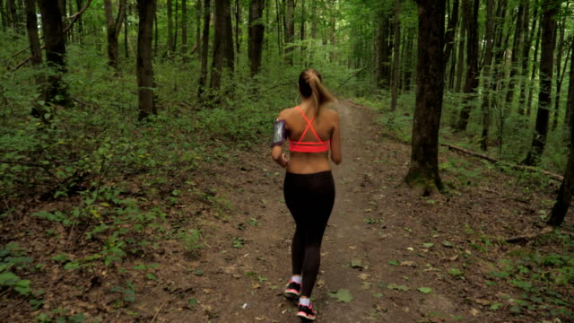 Athletic Woman With Headphones Running On A Forest Track, Sports And Recreation video