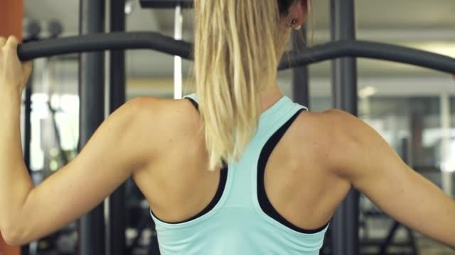 athletische frau, die auf der lat pull down maschine arbeitet - gewichtstraining stock-videos und b-roll-filmmaterial