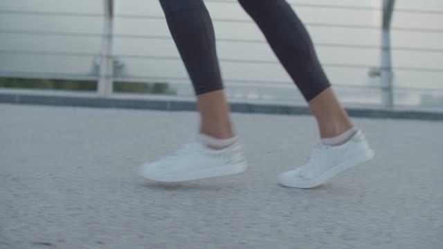 vidéos et rushes de jambes de femme d'athlétisme faisant du jogging sur le pont le matin - joggeuse