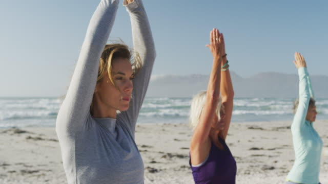 plajda yoga yapan atletik kadınlar - orta yetişkin stok videoları ve detay görüntü çekimi