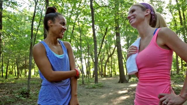 athletic women talking before running outdoors in sunny park - black woman towel workout bildbanksvideor och videomaterial från bakom kulisserna