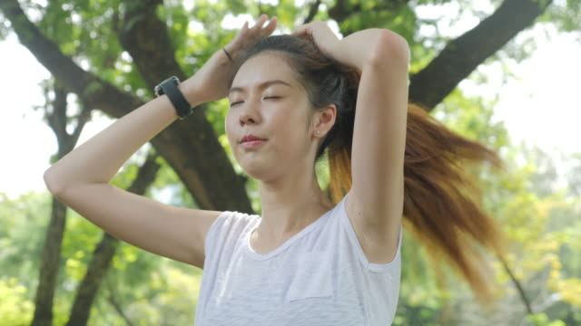 athletic young asian woman straightens her hair before morning run in city park. sports healthy lifestyle concepts. - sudore video stock e b–roll