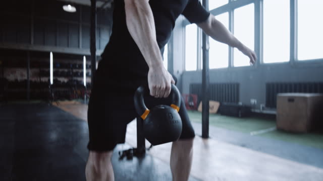athletic young bearded caucasian man during extreme functional workout lifting kettlebell in large gym slow motion. - giria filmów i materiałów b-roll