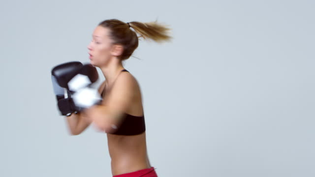 Athletic young blonde woman shadow boxing, shot on R3D video