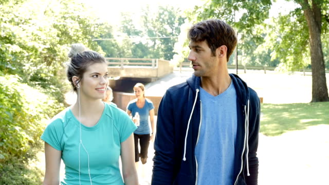 Athletic young couple walking together on track in sunny park video