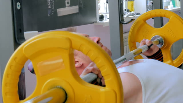 Athletic young man doing exercises with barbell at gym, fitness club video
