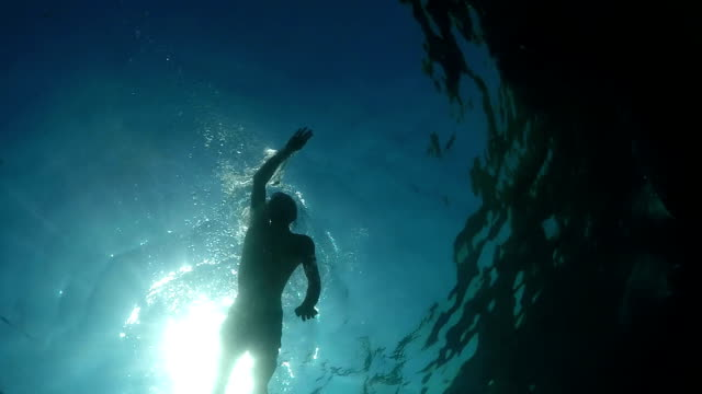 UNDERWATER: Athletic young man swimming crawl in beautiful ocean on sunny day video