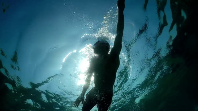 UNDERWATER: Athletic young man swimming crawl on freestyle swimming competition video