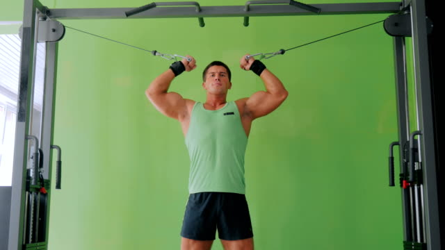 Athletic young man working out on fitness exercise equipment at gym Athletic young man working out on fitness exercise equipment at gym, fitness club. Health, sport and workout concept human joint stock videos & royalty-free footage