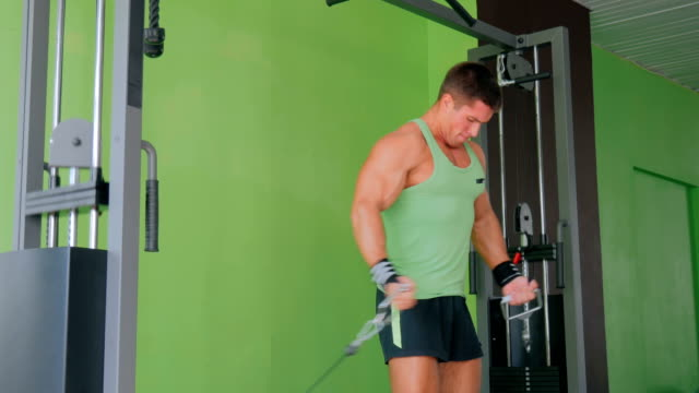 Athletic young man working out on fitness exercise equipment at gym video