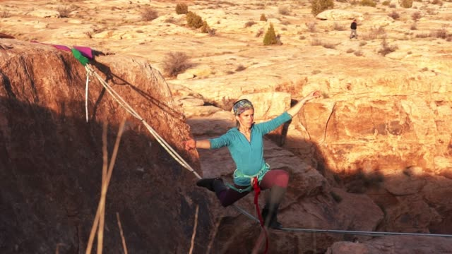Athletic Young Woman Highlining over a Canyon in Moab video