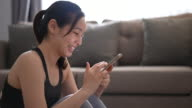 istock Athletic Young Woman is Using a Smartphone while Sitting on a Floor at home 1281975483