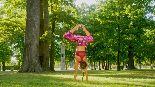 MS Athletic young woman practicing handstand splits in sunny park