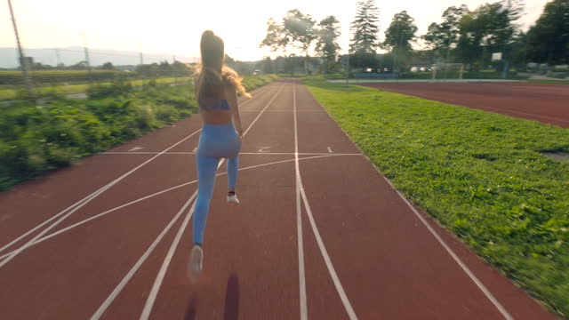DRONE Athletic young woman running on a running track